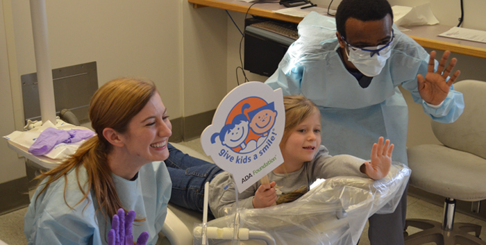 Photo of child and two dental team members, smiling and waving