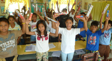 Photo of kids with new toothbrushes and toothpaste in a classroom in the Philippines