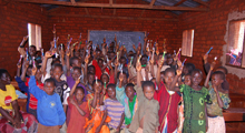 Photo of students with hands raised in a classroom, Tanzania